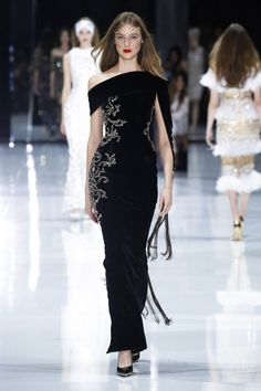 Black velvet gown embellished with metallic gold and smoked topaz stones, featuring an asymmetric sleeve edged in metallic chain tassels and complimented by Swarovski spheres.