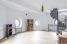 The first floor with spiral staircase. Antique light fixtures that come with the home were once affixed to a horse-drawn carriage belonging to the Swedish royal court.