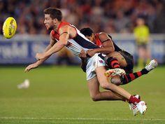 Alwyn Davey (r) von Essendon hängt sich an Jeremy Howe aus Melbourne. Nach dem Regelwerk im Australian Football ist das kein Verstoß. (Foto: Joe Castro/dpa)
