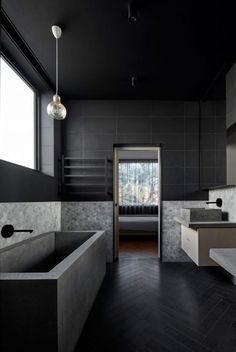 This Australian home has two bathrooms, including one that features a concrete tub and decorative grey tiling.