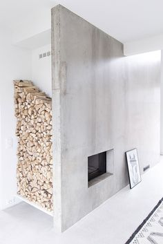 Amazing way to store logs next to a fire that becomes part of the decor. Brilliant concrete fireplace too.