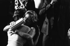 Black and white photo of a mother hugging her daughter at her wedding.