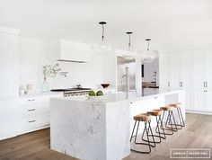 Stark white kitchen with marble island, rustic wood stools, and bulb lighting