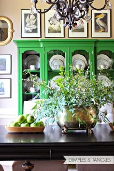 neutral dining room with a pop of green, artwork placed above the china cabinet from Dimples and Tangles blog