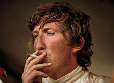 Jochen Rindt smokes a cigarette in the pits. Championship: Formula 1 1970 Event: Austrian GP Date taken: Sunday, August 1970 Location: Red Bull Ring, Austria Photographer: Rainer Schlegelmilch F1 Racing, Racing Team, Formula 1, Jochen Rindt, Gilles Villeneuve, Lancia Delta, Racing Events, F1 Drivers, Photo Search