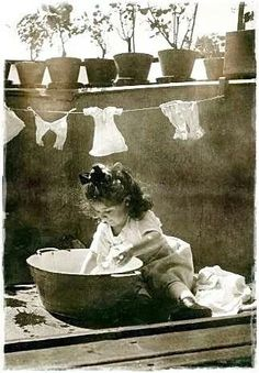 Little girl washing her dolls clothes in a tin bath how sweet..