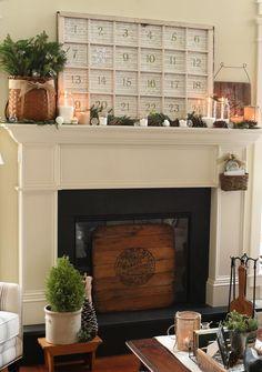 déco de manteau de cheminée pour Noël - un calendrier de l'Avent, des bougies, des branchettes vertes et des pommes de pin