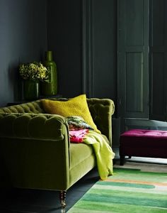 Green tufted sofa, dark grey walls, and fuchsia accents.  Via: greige: interior design ideas and inspiration for the transitional home