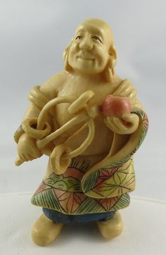 "Antique Japanese Hand Carved Ivory Netsuke, polychrome ivory of man holding instrument. Measures - 2 1/8"" high."