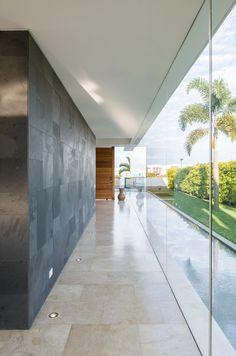 El corredor contra la zona exterior de la casa está acompañado de un largo espejo de agua y delimitado por un muro enchapado en piedra pizarra negra que lo separa de la cocina.