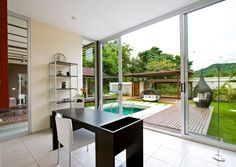 If you have a welcoming outdoor space, make the most of it by connecting it with indoor living spaces in your home. This study opens up to a relaxing pool area with a sliding stacking door.