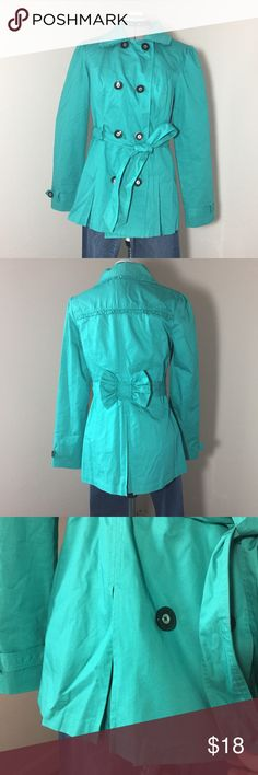 """🆕Listing: Candies Spring Green Trench Jacket Candies Spring Green Trench Jacket. Color can be more blue or green depending on the light. Shown in natural light, no photo app used. Size Juniors M measures: 15"""" across shoulders, 18"""" across chest, 27"""" long, 25"""" sleeve. Ruffle detail along seems, wide pleats on bottom for fullness, bow on back for flirty touch. 4 button close, 2 front pockets, tie at waist. 100% cotton, fully lined. FCrt/031117 Candie's Jackets & Coats Trench Coats"""