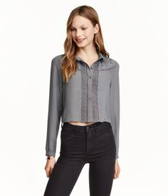 Short, straight-cut blouse in chiffon with embroidery and inset lace trim. Collar, buttons at front, and long sleeves. Narrow cuffs with lace trim and a button.