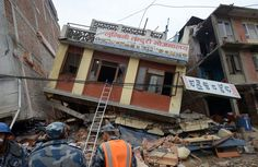 Nepalese rescue personnel observe damaged buildings following the earthquake in Kathmandu on April 26, 2015.