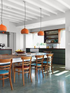 Above the dining room's Hodgson & Barker Antiques table—found on eBay—are ceramic pendant lights from Hand & Eye Studio. The architect acquired the wood chairs secondhand.  Photo by: Damian Russell Courtesy of: Damian Russell