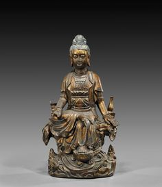 """Tall Chinese, Ming-style, gold lacquered bronze figure; of Guanyin, seated in the position of """"Royal Ease"""": sitting on a naturalistic base with a censer to one side and her bottle of tears to the other, all upon a base of wave motif; H: 23 1/4"""""""