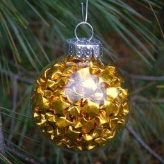 goldene Glückssternchen in einer transparenten Weihnachtsbaumkugel