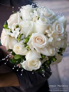 Simple white bridal bouquet featuring white roses, pearls and green accents.