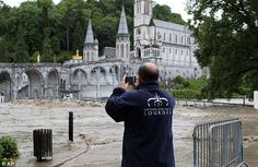Captured on camera: A guardian of Lourdes sanctuary takes a photograph of the area following heavy flooding