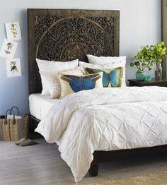 tête de lit en bois massif orné et coussins en papillons