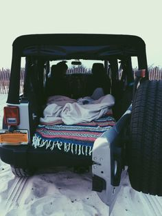 camp out in a jeep on the beach