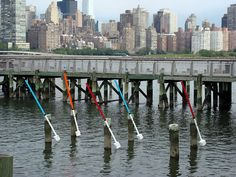 Wave/wind/tide balanced pendulums in Gantry Plaza State Park, on the East River in Long Island City.  These are very relaxing to watch.  They move constantly with the waves, while shifting from horizontal at high tide to upright at low tide.  Again, their paint job is inspired by our research into a maritime aesthetic of fishing bobbers and buoys. -  During low tide.