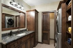Stacked washer/dryer in laundry room with custom cabinets & pocket door. Custom Home Builders, Custom Homes, Dream Home Builder, Lake Homes, Pocket Doors, Twin Cities, Custom Cabinets, Dryer, Washer
