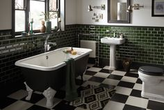 Heritage Bathrooms Wynwood suite with Dorset Free Standing cast iron bath, bottle green wall tiles, Edgeware mirror in slate grey and graphic print mat