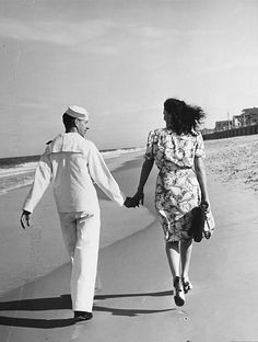 A sailor and his date taking a walk along the beach (1942) ~