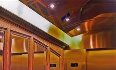 Mirrored Brass Concave Ceiling at UofT's Historical Hart House. Perimeter lighting with recessed down lights provides a balance of diffused and direct light inside this Elevator Interior.