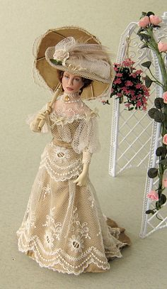 1895l. She wears a gold silk dress, overlaid with silk tulle and cotton lace