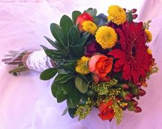 Early Autumn bridesmaid's bouquet. Clutch style featuring gerbera daisies, spray roses, button mums, hypericum berries and solidago.