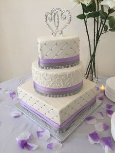 3-tier buttercream wedding cake with lavendar and silver accents. Square, round and heart shaped cakes.