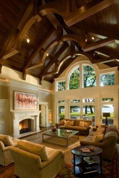 A Fabulous Living Room Features Vaulted Ceiling Of Wood And Exposed Beams With Center Barrel Shape That Mimics The Arched Transom Window Above