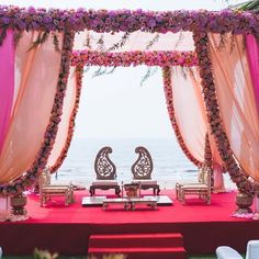 Curated by WeddingSutra Favorite @knotmarried, this mesmerizing floral mandap with flowing drapes overlooking the sea will give you major #beachweddinggoals.     #weddingphotography #weddingdecor #decortrends #decorinspo #weddinginspiration #trendalert #decorinspiration #decorideas #weddingideas #weddingsutra #weddingdecor #decorideas #drapes #mandap #weddingplanning #weddingelements...