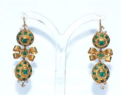 High carat gold Spanish earrings set with foiled table-cut emerald paste, circa 1820. The earrings are in the traditional Iberian form of bows and pendant drops which was popular throughout the 18th century and into the 19th century.