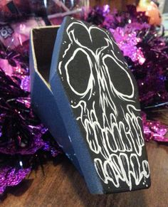 Cute little coffin box to hold your tiny little things in!Hand painted paper mache craft box. Acrylic paint.-Black painted box with white skull outlines.-Inside is NOT painted, as not to ruin anything you put inside
