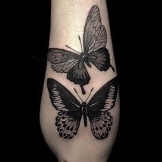 black work butterfly tattoo on the forearm