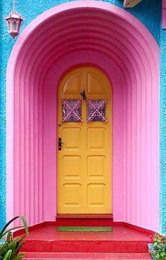 Para quem gosta de ousar! Esta é uma porta que, com um amarelo vibrante, contrasta com cores não menos vibrantes da fachada. Décor para quem não tem medo de arriscar e que pode dividir opiniões!