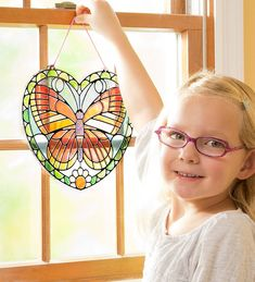 Stained Glass Butterfly Heart Kit - Create a luminous butterfly to light up your window just like stained glass would! This kit includes a colorful butterfly-heart design in peel-and-stick stickers kids can transfer to a clear frame with grooves and outlines that match the colorful stickers. Cord and suction cup for hanging included. #butterfly #kidsart #valentinesday