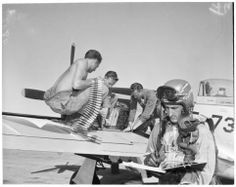 Airman 2/C Jack Corathers; Airman 2/C Douglas Howard; T/Sgt. Marvin Bertram and Capt. Eusebio Arriaga, 32, ex-Sun Valley ski instructor, at plane that is being equipped with .50 cal. bullets.   Victorville layout, 1952 :: Los Angeles Examiner Collection, 1920-1961