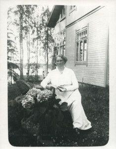 Maija Dunderberg istuu kirja kädessä Dunderbergien omistaman Toskala -huvilan pihassa. 1900-luvun alkua. Vapriikin kuva-arkisto.