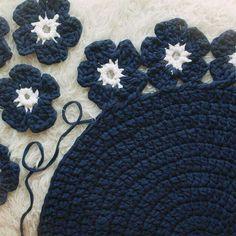 Alfombra en crochet con flores por el borde . azul marino