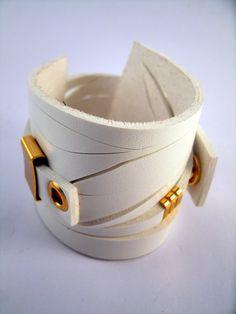 Pulseira de couro sintético branca com cortes horizontais vazados e metal dourado Temos este modelo de pulseira tambem nas cores: beje,preta,marrom,cobre,vermelha,laranja e ocre. Deixe uma mensagem jun...