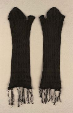 Knitted black mitts with vertical openwork bands; black cord trim at finger and thumb openings, fringe at arm opening; flap lined with black silksatin.