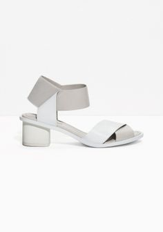 These mid-heel leather sandals are detailed with inventive folded straps that create a clean, yet fanciful look.
