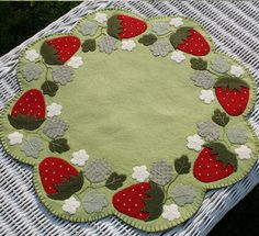Scalloped Folk art Strawberry Wool Table Mat with appliqued berries Blanket stitch edge and fabric backing. $39.00, via Etsy.