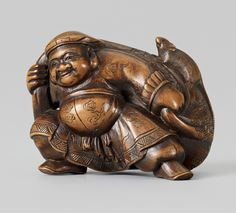 A boxwood netsuke of Daikoku with a bagful of rats, by Masayoshi. Second half 19th century     Running with legs wide apart, he shoulders a large bag with rats crawling in and out of the sack. The eye pupils of black horn. Signed Masayoshi saku.   Height 3.8 cm; width 5 cm