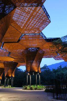 """Orquideorama : plan:b  """"Die wabenförmige Metallstruktur ist mit Lamellen aus Pinienholz verkleidet und verhindert so die direkte Sonneneinstrahlung – eine Schattenspender, dessen Funktion im Urwald von besonders hohen Bäumen übernommen wird. Grossflächige Polyesterpfannen sammeln das Regenwasser, das dann über ein Röhrensystem dosiert in den Boden geleitet wird. Die sechseckige Grundform der Elemente macht die Überdachung flexibel und an die Entwicklung d"""
