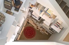 Designer Sallie Trout built shelves in an inaccessible stairwell. She reaches them by using a bosun's chair that is fastened to a chain hoi...